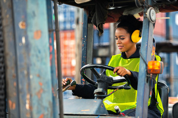 Female worker driving forklift in industrial container warehouse. Wall mural