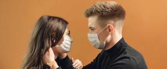 People in the cafe with face mask. Concept with copy space on brown background. Young love couple cuddles. Photo with hugs.