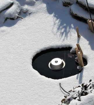 View of a Koi pond covered with snow and an electric pond heater melting the ice
