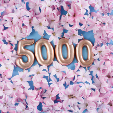 1000 followers card. Template for social networks, blogs. Background with pink flower petals.