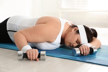 Lazy overweight woman with dumbbells sleeping on mat instead of training at gym