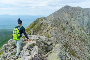 Woman hiking along Knife Edge Trail of Mount Katahdin Northeast Piscataquis Maine USA