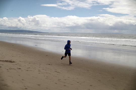 A man runs on the beach during the global outbreak of coronavirus disease (COVID-19) in Santa Monica