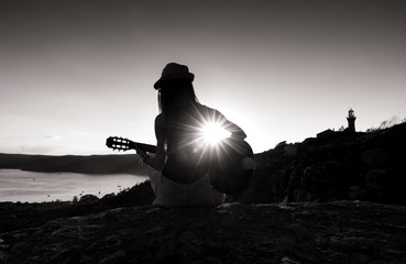 Black and white photo of a guitarist girl at sunset, Palm Beach Australia