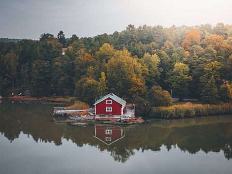 Lonely red cabin at a lake in Sweden during fall