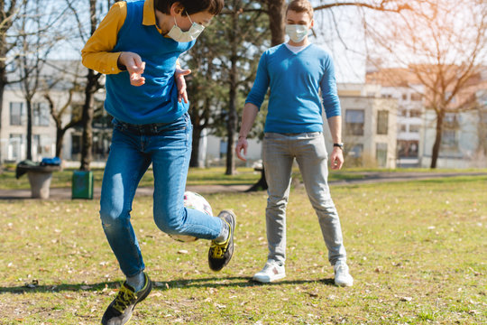 Dad and son playing soccer in park during coronavirus crisis