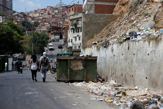 People walk past uncollected garbage as Venezuelan utilities have hiked fees while the economy deteriorates further due to the spread of coronavirus disease (COVID-19) and the crash in global oil prices, in Caracas