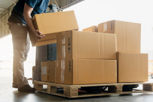 Worker courier lifting package boxes stack on pallet, warehouse delivery service shipment goods