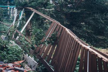 台風災害被害。壊れた木の塀と落ちて割れた瓦