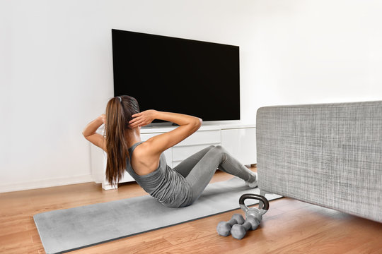 Home fitness workout class live stream online. Woman doing strength training abs situps bodyweight floor exercises watching videos on a smart tv in the living room of apartment.