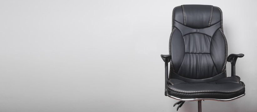 Black leather office chair in grey background.