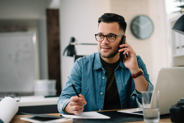 Businessman in office. Handsome man talking on phone at work.