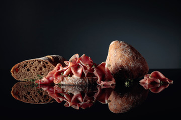 Fototapete - Prosciutto with ciabatta and thyme on a black background.