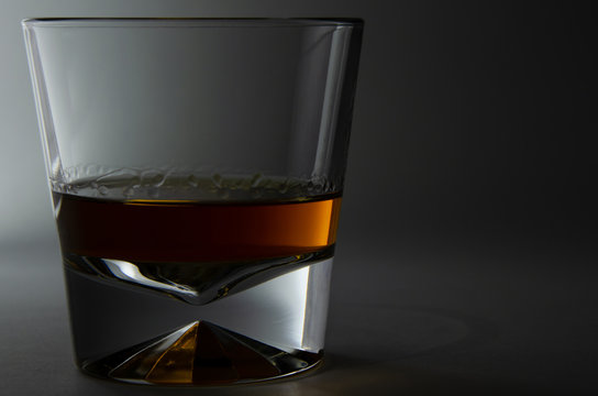 glass of whiskey and ice on black background