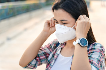 Asian woman wearing N95 mask to protect pollution PM2.5 and virus. COVID-19 Coronavirus and Air...