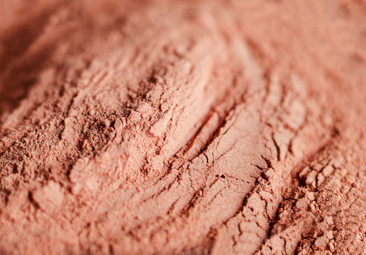 Red bentonite clay powder. Natural beauty treatment and spa background. Clay texture close up, selective focus.