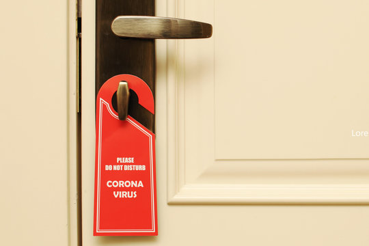 """On the handle hangs a """"do not disturb, coronavirus"""" sign. Quarantine at the hotel, dangerous travel. Business trip to other countries. Isolation, stay home."""