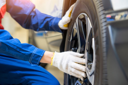 Auto mechanic changing tire outside,Car service.Hands replace tires on wheels.Tire installation concept.