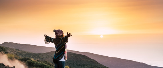 Fototapeta Freedom and hope concept with successful woman on the top of the world open arms and hug a beautiful colored sunset in front of her - concept of victory and win people in outdoor nature beauty obraz