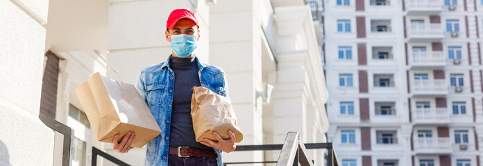 Delivery man holding paper bag with food on white entrance of house background , food delivery man in protective mask