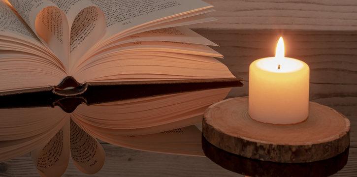 Livre plié en forme de cœur sur fond de bois.