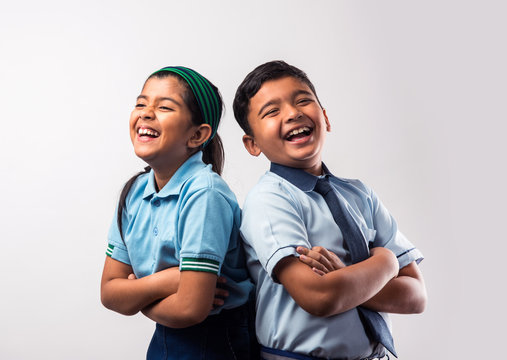 Cheerful Indian school kids in uniform standing isolated over white background