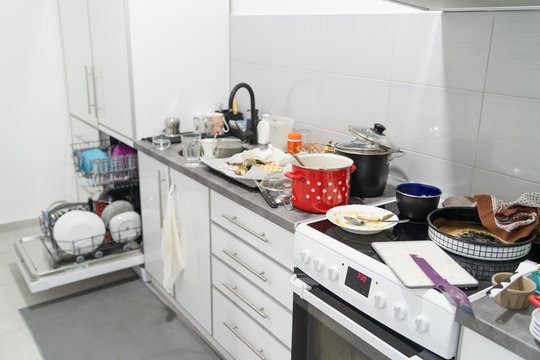 Side view on white kitchen with unwashed dirty pots and dishes on the countertop utensils and kitchen appliances in a mess after cooking