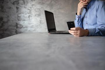 Fototapeta Postura mężczyzny pracującego przy komputerze trzymający w dłoni telefon komórkowy obraz