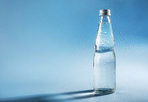 Glass water bottle on blue background