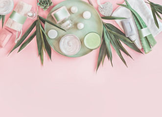 Fototapeta Modern beauty and skin care. Various natural cosmetic products with bamboo branches and aloe vera leaves. Eco friendly body care and spa accessories on pastel pink background. Zero waste . Top view obraz