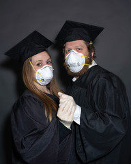 2 quarantined coronavirus COVID-19 graduate students with masks in graduation cap and gown for cancelled commencement ceremony