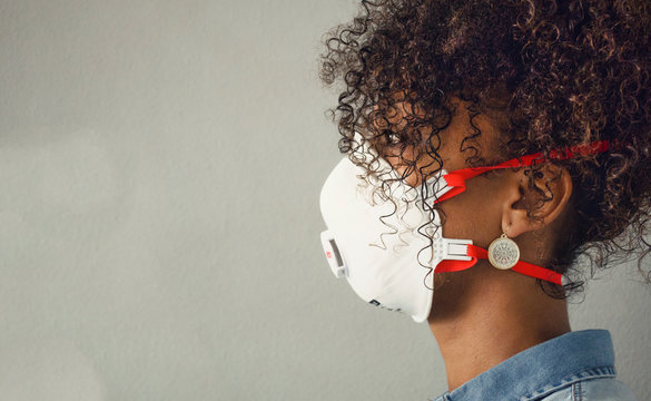 Profile of a black woman wearing a FFP3 mask with an exhalation valve. Coronavirus. Protection.  Copy space.
