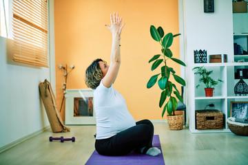 Mid-adult fit pregnant Caucasian woman practicing prenatal yoga exercises. Morning time.
