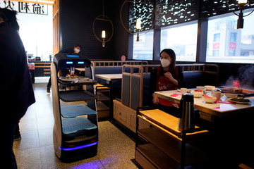 Robot transports food to serve to diners at a restaurant, following an outbreak of the novel coronavirus disease (COVID-19), in Shanghai