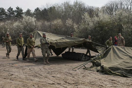 Soldiers erect tents for a ROL 2 class mobile military hospital that will tend to patients infected with the coronavirus disease (COVID-19), in Otopeni