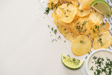 top view of potato chips with salt near sliced lime and garlic sauce on white