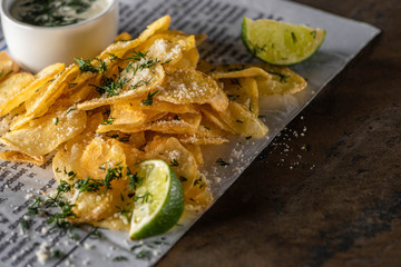 selective focus of potato chips with salt near sliced lime, garlic sauce and newspaper on marble surface
