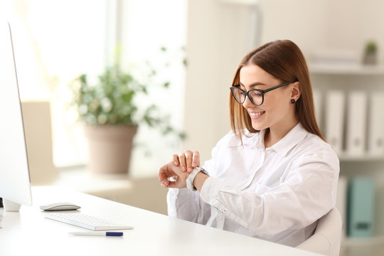 Young woman looking at her watch in office