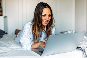 Delighted woman using laptop on bed