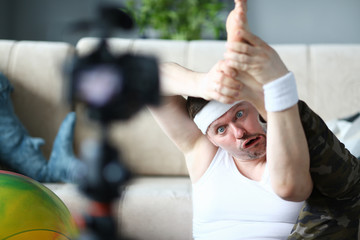 Blogger Man with Funny Face Doing Exercise for Leg. Male Recording Fitness Video on Digital Camera for Sport Blog. Ridiculous Sportsman Practice Gymnastics Aerobic for Stretching in Apartment