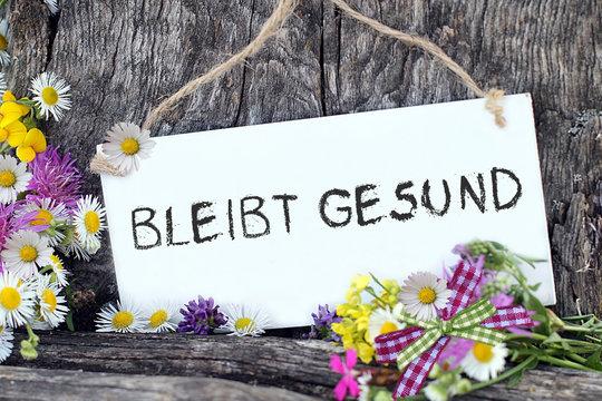 Bleibt Gesund als Schriftzug auf weisser Tafel mit Blumen in der Natur