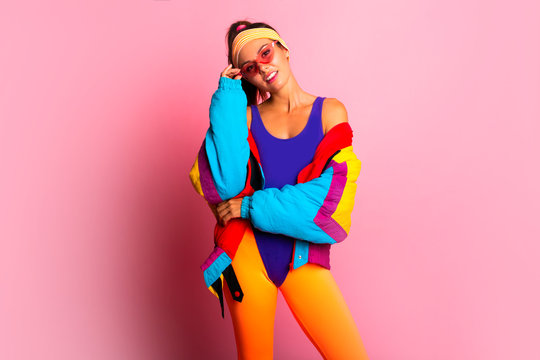 Back in time 90s 80s. Stylish girl in retro colourful  vintage coat, orange leggings, and purple body, fashion trends, entertainment. 80's Fashion woman over pink background. Beautiful athletic girl.