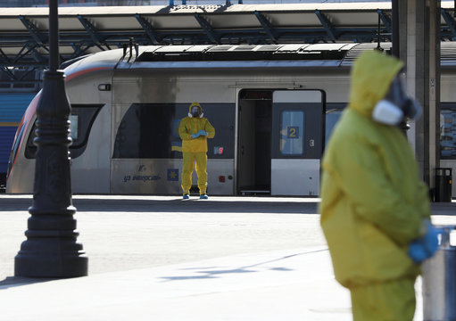 Employees wearing protective suits are seen near the train which evacuated Ukrainian citizens from Poland, in Kiev