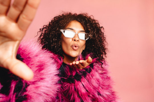 Indoor self portrait of young pretty african hipster girl wearing pink faux fur trendy coat and stylish sunglasses ,smiling, laughing, making selfie joy,positive emotions. Gesture, v sign.