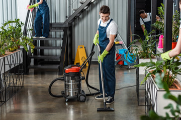Obraz young cleaner cleaning floor with vacuum cleaner near multicultural colleagues - fototapety do salonu