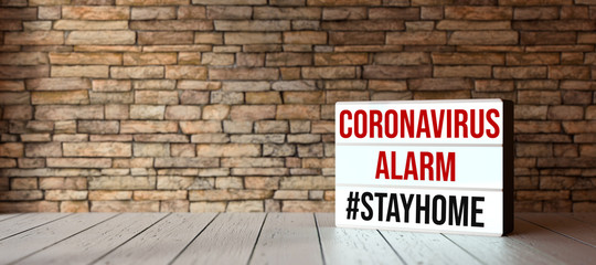 Fotorolgordijn Londen lightbox with text CORONAVIRUS ALARM #STAYHOME in front of a brick wall on wooden floor