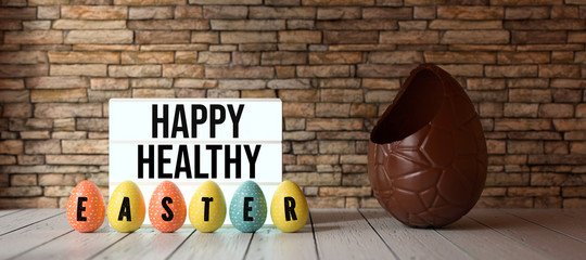 easter eggs with message HAPPY HEALTHY EASTER with big chocolate egg in front of a brick wall