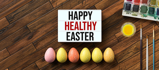 easter eggs with message HAPPY HEALTHY EASTER surrounded by brushes and water color boxes on wooden...
