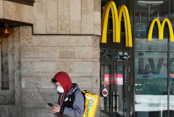A Glovo food delivery courier wearing a protective mask checks an order outside a McDonald's restaurant in central Kiev