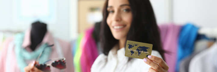 Focus on female hand holding bank credit card. Lady standing in modern clothes store with multicolored bags with new outfits. Gorgeous lady looking at camera with happiness. Shopping concept